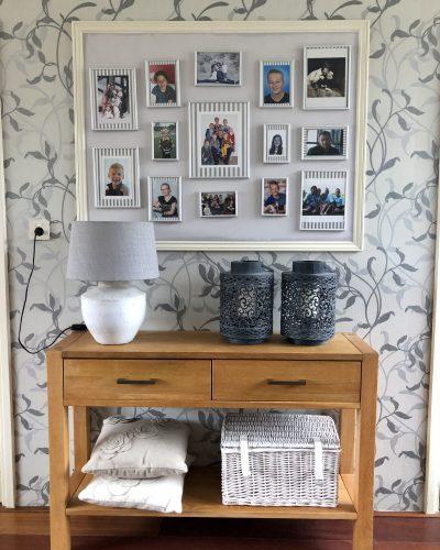 Combinatie van behang en een persoonlijke fotogalerij in de woonkamer.